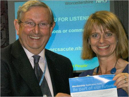 Harriett Baldwin hands her membership form to Michael O'Riordan, Chairman of the Worcestershire Acute Hospital Trust